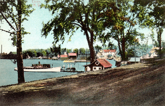Rosslyn bathhouse, boathouse, and the steam yacht, Kestrel, are center foreground, the Old Dock is center background with Essex Horse Nail Co. Factory at far left. (Source: Shirley LaForest via Essex on Lake Champlain)